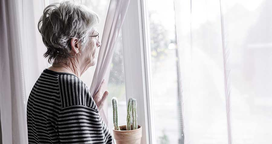 sad elderly woman looking out a window